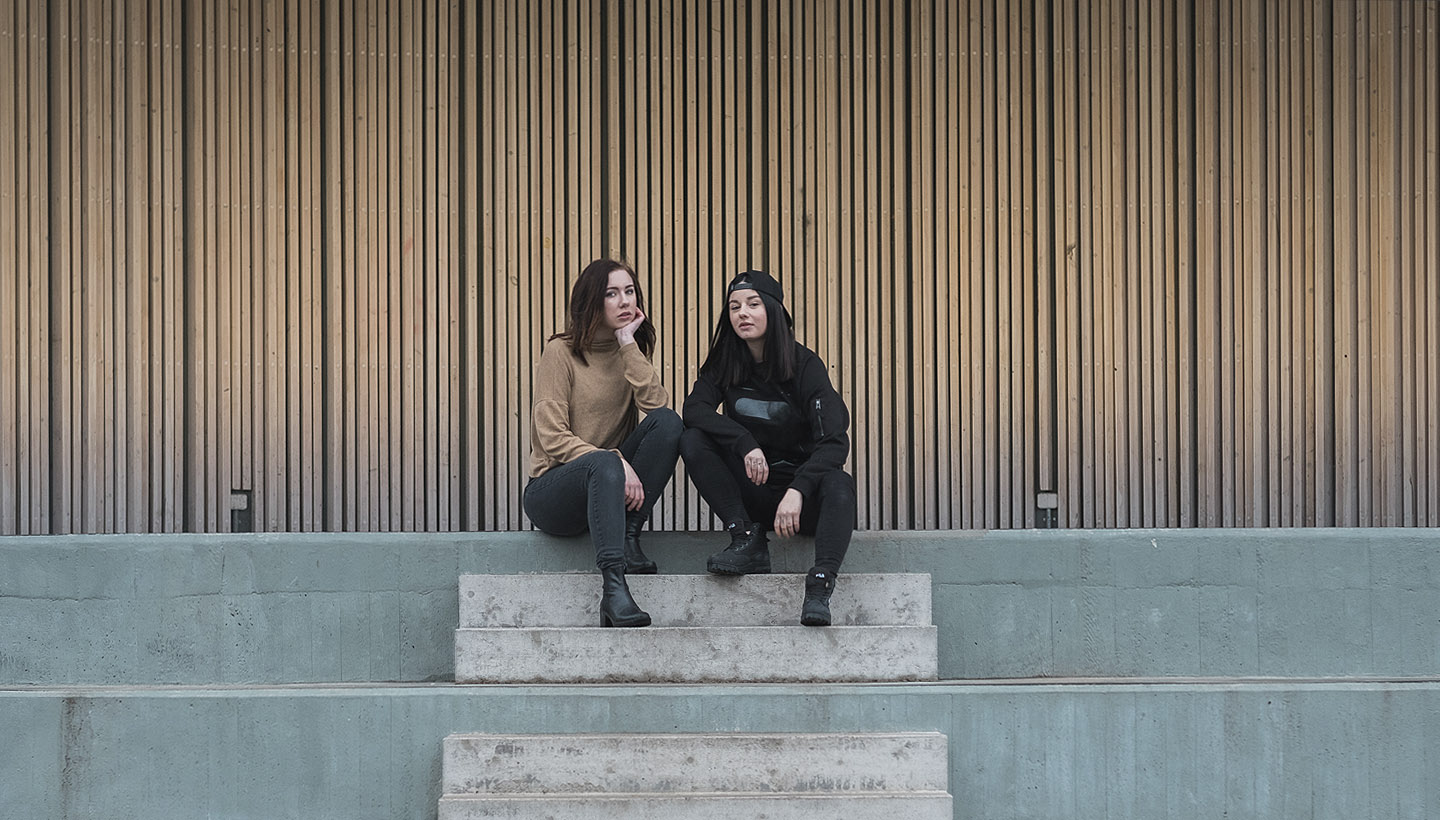 Image: two girls sitting on concrete steps