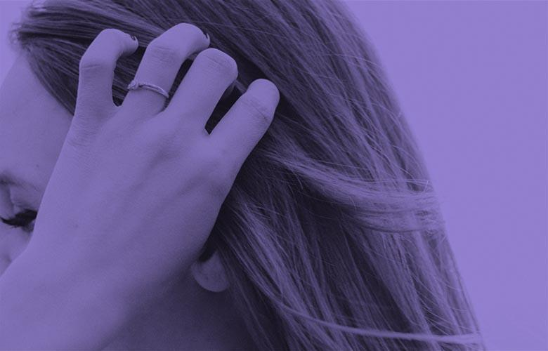 Image: purple photo of someones hand moving hair out of their face