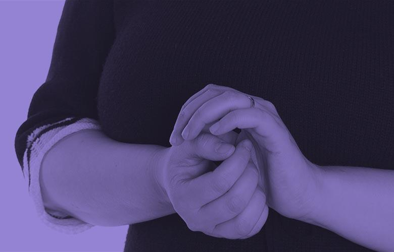 Image: purple photo of a persons hands touching eachother nervously