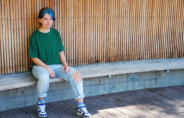 Image: non binary trans person sitting on a park bench