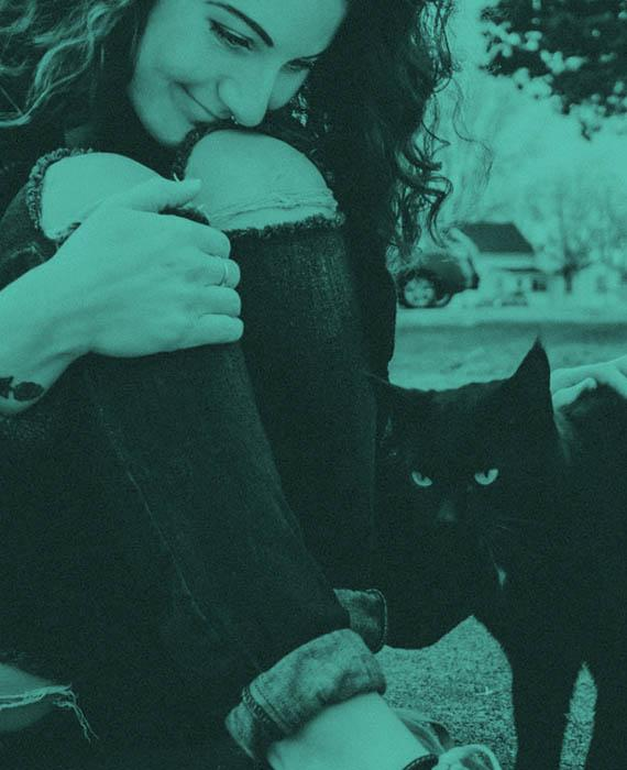 Image: girl outdoors petting a black cat